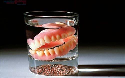 Ngâm hàm răng giả trong nước muối sinh lý 0.9% để làm sạch